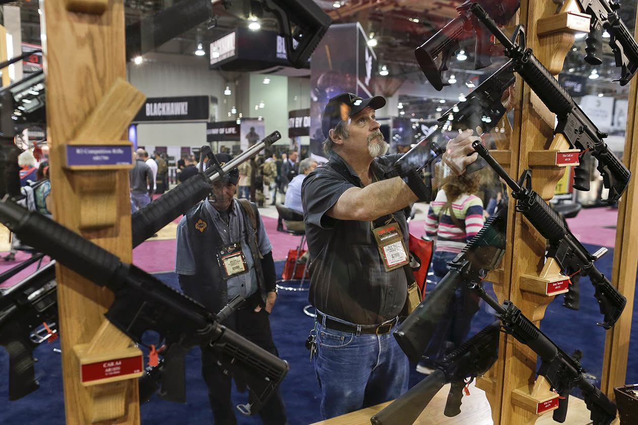 David Corley of Shreveport, La., replaces a rifle on its display rack while browsing through the Rock River Arms display booth.