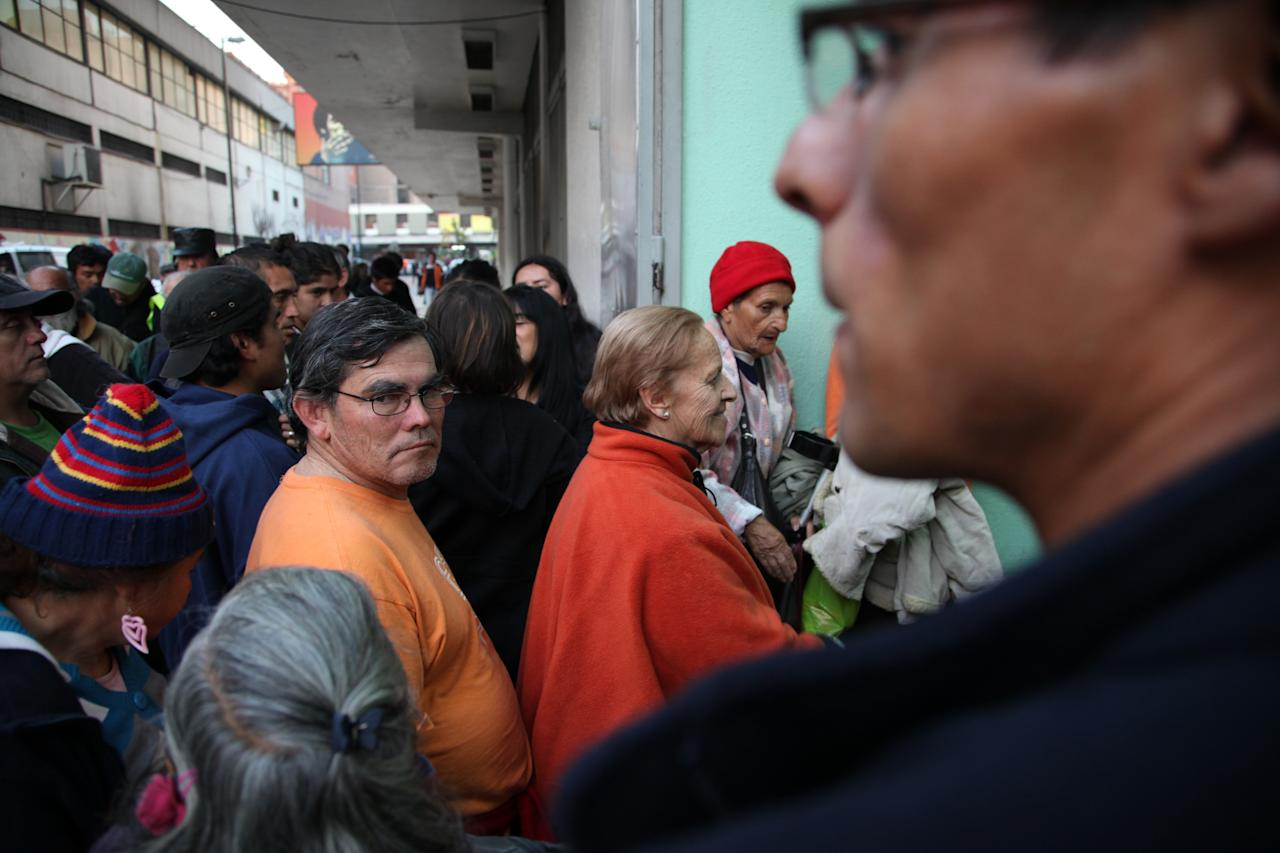 "In this May 24, 2013 photo, Ana Luisa Villarroel, 78, center right, waits in line to be one of the first to enter the homeless shelter at the indoor stadium Estadio Victor Jara in Santiago, Chile. This is her first night at the shelter after she left what she described as an abusive situation at her family's home. This emblematic stadium, which hosts sporting events throughout the year, was where Chilean folk singer Victor Jara was tortured and killed on Sept. 14, 1973, just days after the military coup. ""For me, it's a miracle to be here where they are now giving shelter and food to everyone and where they killed Victor Jara,"" said Ana Luisa Villaroel, 78, who lived through the dictatorship. (AP Photo/Brittany Peterson)"