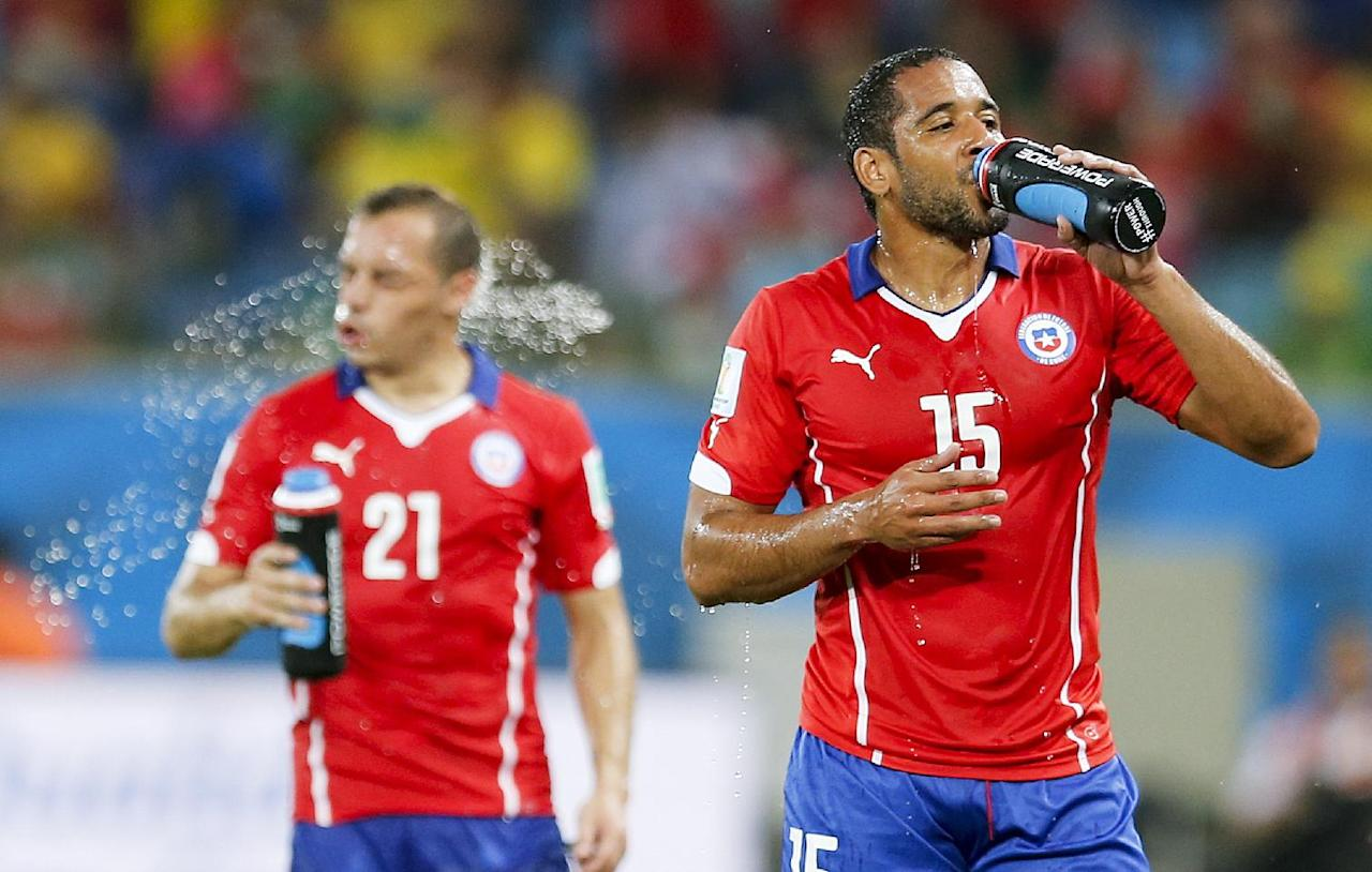 Chile's Jean Beausejour, right, and Marcelo Diaz take a drink during the group B World Cup soccer match between Chile and Australia in the Arena Pantanal in Cuiaba, Brazil, Friday, June 13, 2014.  (AP Photo/Frank Augstein)