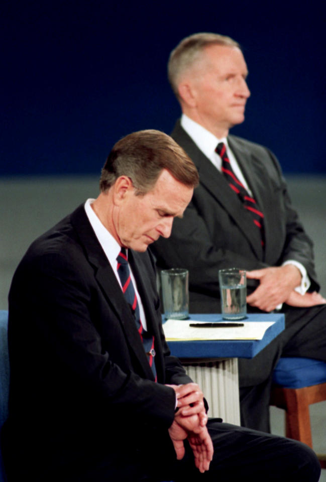 """FILE - In this Oct. 15, 1992, file photo President George H.W. Bush looks at his watch during the 1992 presidential campaign debate with other candidates, Independent Ross Perot, top, and Democrat Bill Clinton, not shown, at the University of Richmond, Va. The """"town hall"""" style presidential debates began 20 years ago as a nerve-racking experiment in live television. Moderator Carole Simpson was so nervous about turning over the microphone to regular folks that she spent days mapping out the presidential candidates and their issues on 3-by 5-cards, just in case. Viewers want the candidates to show respect for those voters in the room, who stand in proxy for all Americans. Bush was thrown by a women's oddly and even worse just as she began her question, TV cameras caught Bush checking his watch. That gesture would be replayed over and again as evidence that the president was indifferent and out of touch. """"I took a huge hit,"""" Bush said years later. (AP Photo/Ron Edmonds, File)"""