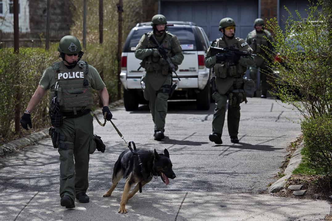 Heavily armed police officers do house to house searches in the neighborhoods of Watertown, Mass. Friday, April 19, 2013, as a massive search continued for one of two suspects in the Boston Marathon bombing. A second suspect died in the early morning hours after an encounter with law enforcement. (AP Photo/Craig Ruttle)