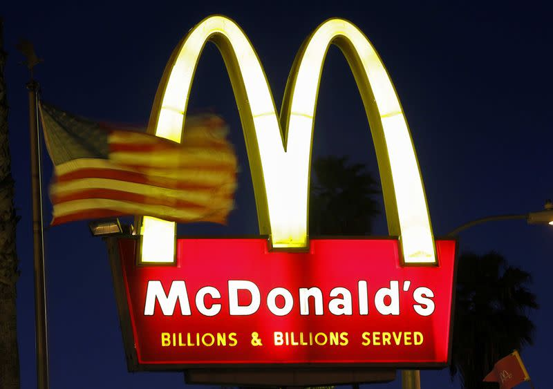 File photo of a U.S. flag fluttering in the wind in front of a sign for a McDonald's restaurant in Los Angeles