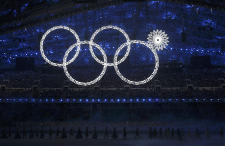 Participants march by as one of tne of the Olympic Rings fails to completely illuminate during the opening ceremony of the 2014 Sochi Winter Olympics