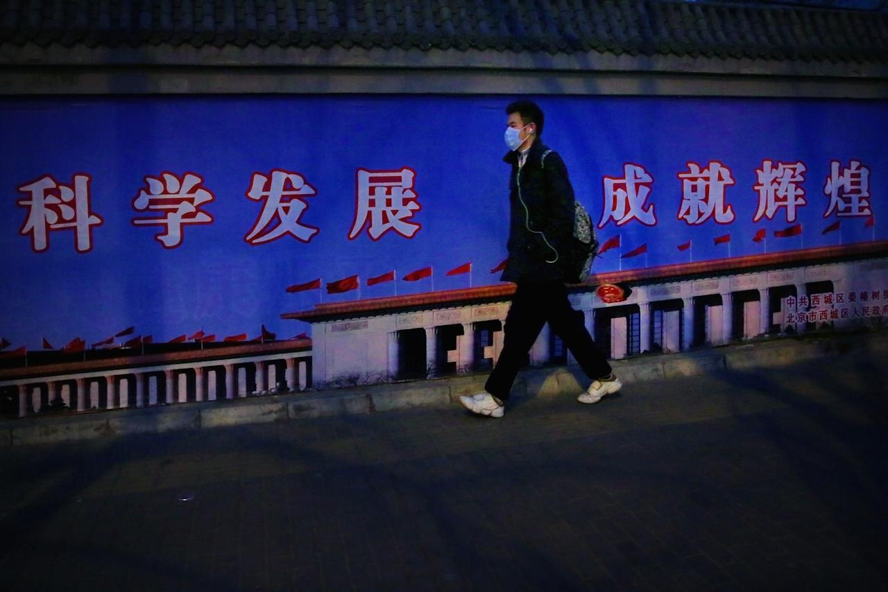 BEIJING, CHINA - FEBRUARY 28: A young man wearing the mask walks along the wall with the picture of the Great Hall of the People during severe pollution on February 28, 2013 in Beijing, China. Beijing was hit by its first sandstorm of the year while its air quality reached dangerous level on Thursday.  (Photo by Feng Li/Getty Images)