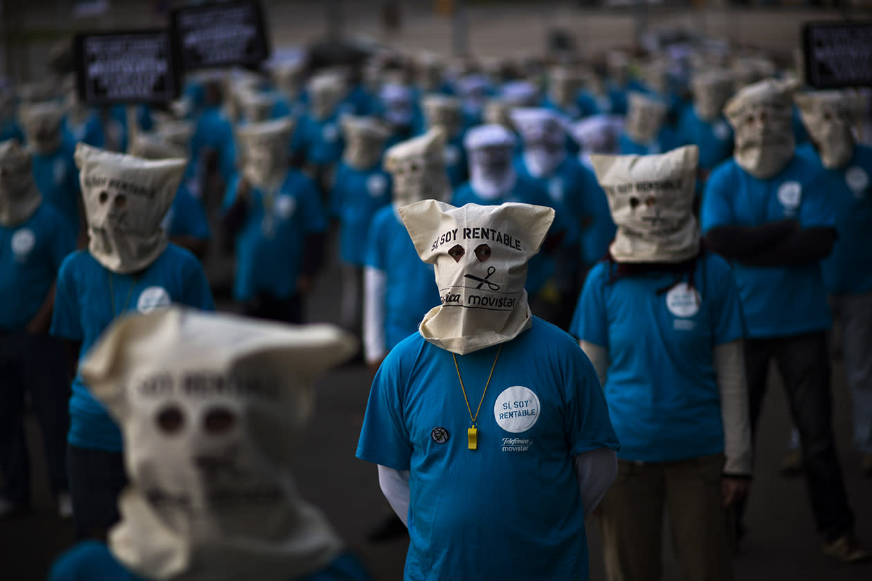 Masked demonstrators, employees from the Telefonica phone company, are seen reflected in a glass window as executives from the same company take part in a business meeting in Barcelona.