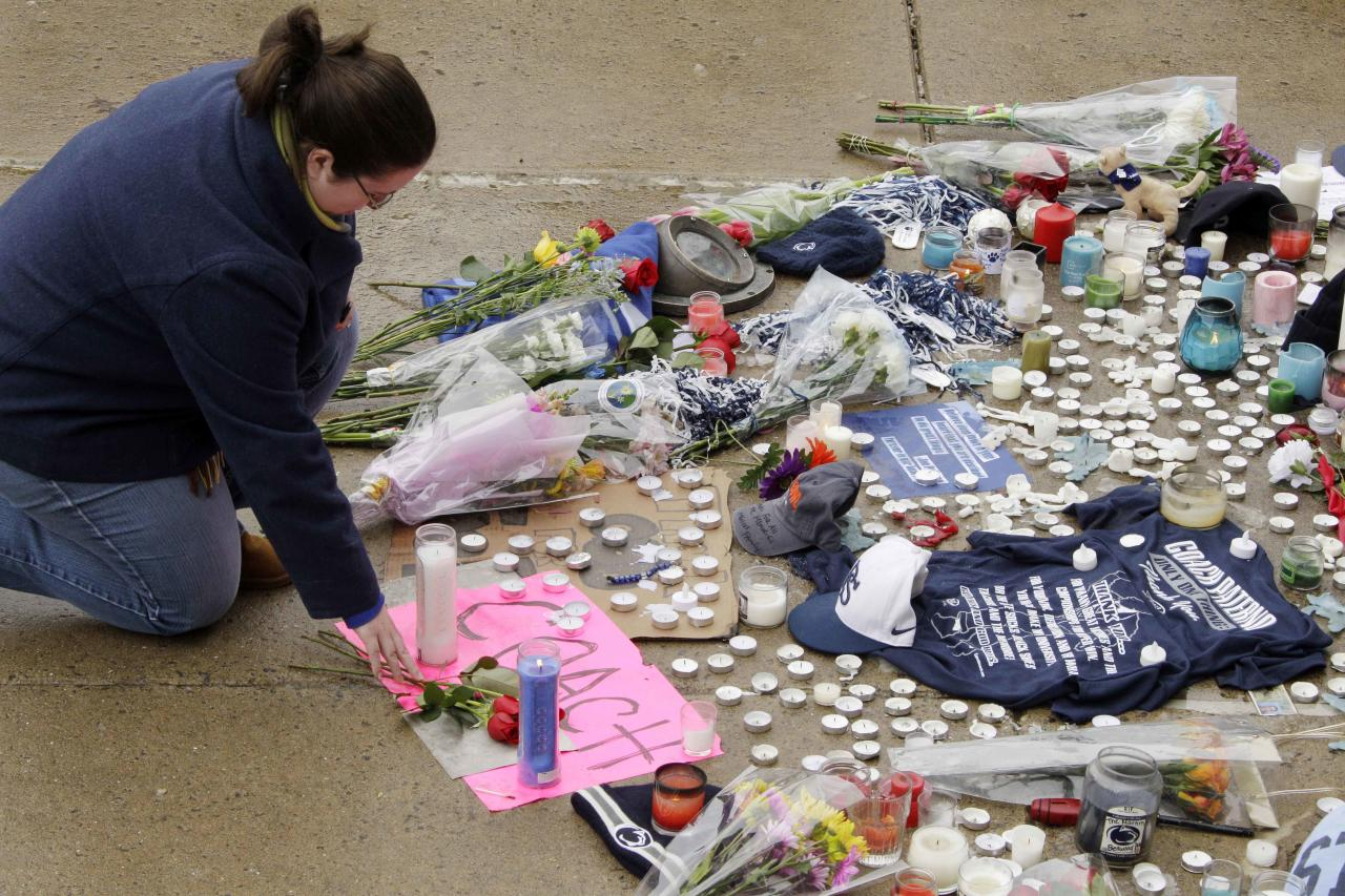 Laura Scott, of State College, Pa., places a rose at the foot of a statue of Joe Paterno outside Beaver Stadium on the Penn State University campus after learning of his death Sunday, Jan. 22, 2012, in State College,Pa. (AP Photo/Gene J. Puskar)