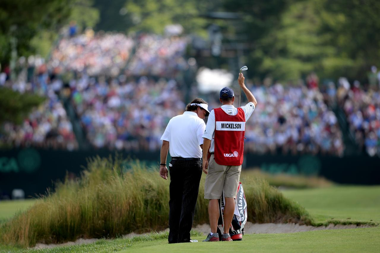 ARDMORE, PA - JUNE 14: Phil Mickelson of the United States prepares to play his second shot on the fifth hole alongside Jim 'Bones' Mackay uring Round Two of the 113th U.S. Open at Merion Golf Club on June 14, 2013 in Ardmore, Pennsylvania. (Photo by Ross Kinnaird/Getty Images)