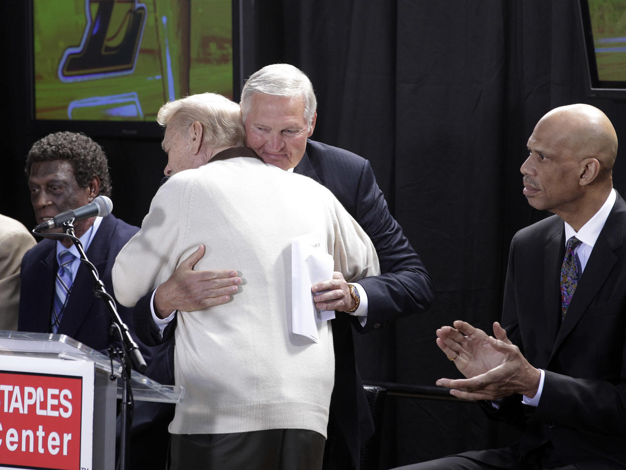 Former Laker Jerry West, center facing camera, hugs Los Angeles Lakers owner Jerry Buss as they are joined by former Lakers Elgin Baylor, left, and Kareem Abdul-Jabbar during the unveiling ceremony of a statue of West outside Staples Center in Los Angeles, Thursday, Feb. 17, 2011.
