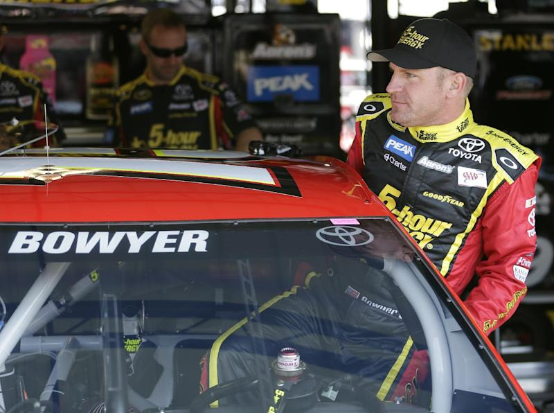 Clint Bowyer climbs into his car before a NASCAR Sprint Cup series auto race practice at Darlington Speedway in Darlington, S.C., Friday, April 11, 2014