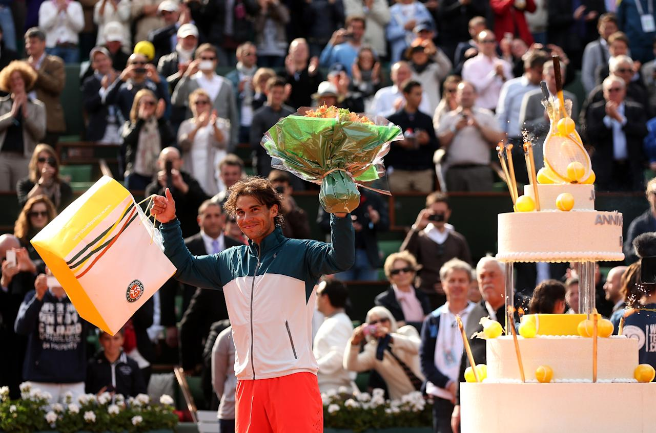 PARIS, FRANCE - JUNE 03:  Rafael Nadal of Spain waves to the crowd after being presented with a birthday cake after victory in his Men's Singles match against Kei Nishikori of Japan during day nine of the French Open at Roland Garros on June 3, 2013 in Paris, France.  (Photo by Matthew Stockman/Getty Images)