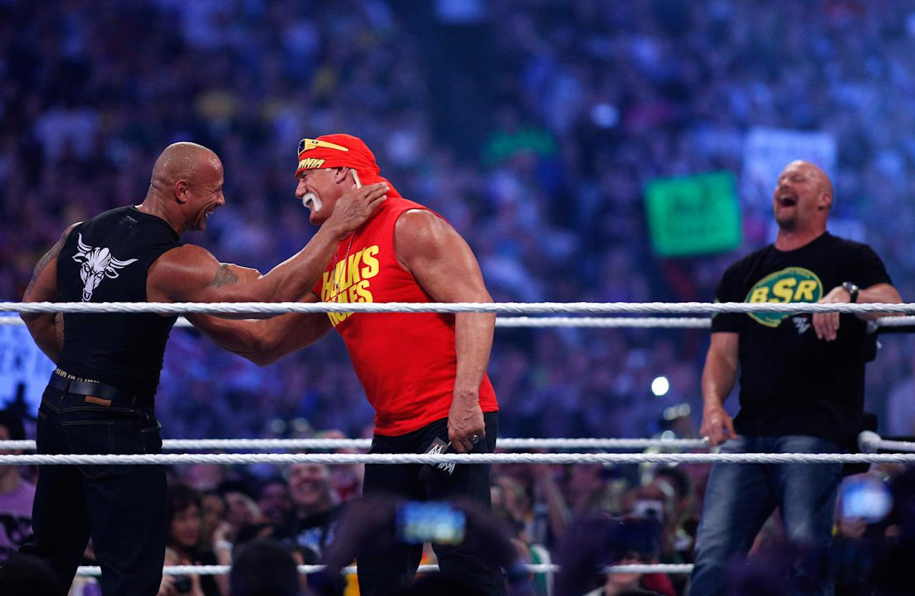 """IMAGE DISTRIBUTED FOR WWE - Dwayne Johnson aka The Rock, left, embraces Hulk Hogan, center, as """"Stone Cold"""" Steve Austin looks on during Wrestlemania XXX at the Mercedes-Benz Super Dome in New Orleans on Sunday, April 6, 2014. (Jonathan Bachman/AP Images for WWE)"""