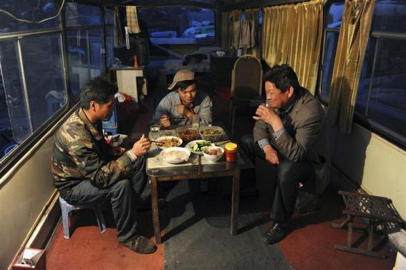 Residents have dinner in a renovated scrapped vehicle which serves as their dwelling, at a dismantling centre for old vehicles on the outskirts of Hefei, Anhui province, China, April 12, 2011. Seven families in the center, with ages from 4 to 84, dismantle old cars as their livelihood during the day and live in renovated scrapped vehicles during the night, local media reported.
