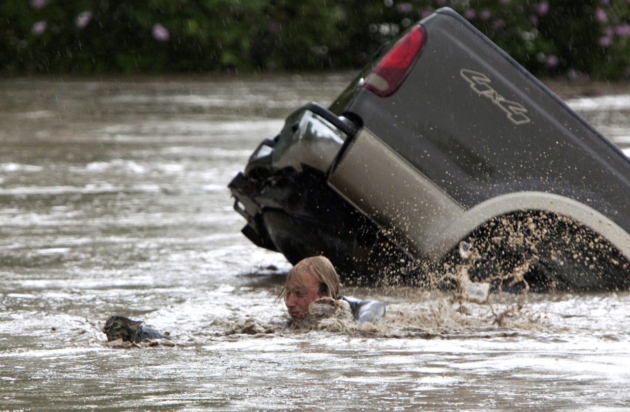Kevan Yaets swims after his cat Momo to safety as the flood waters sweep him downstream after submerging his truck in High River, Alberta on Thursday, June 20, 2013 after the Highwood River overflowed its banks. Hundreds of people have been evacuated with volunteers and emergency crews helping to aid stranded residents. (AP Photo/The Canadian Press, Jordan Verlage)