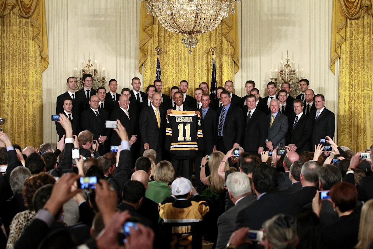 President Barak Obama holds up a Boston Bruins hockey jersey during a ceremony where he honored the 2010-2011 Stanley Cup champion Boston Bruins hockey team, Monday, Jan. 23, 2012, in the East Room of the White House in Washington. (AP Photo/Haraz N. Ghanbari)