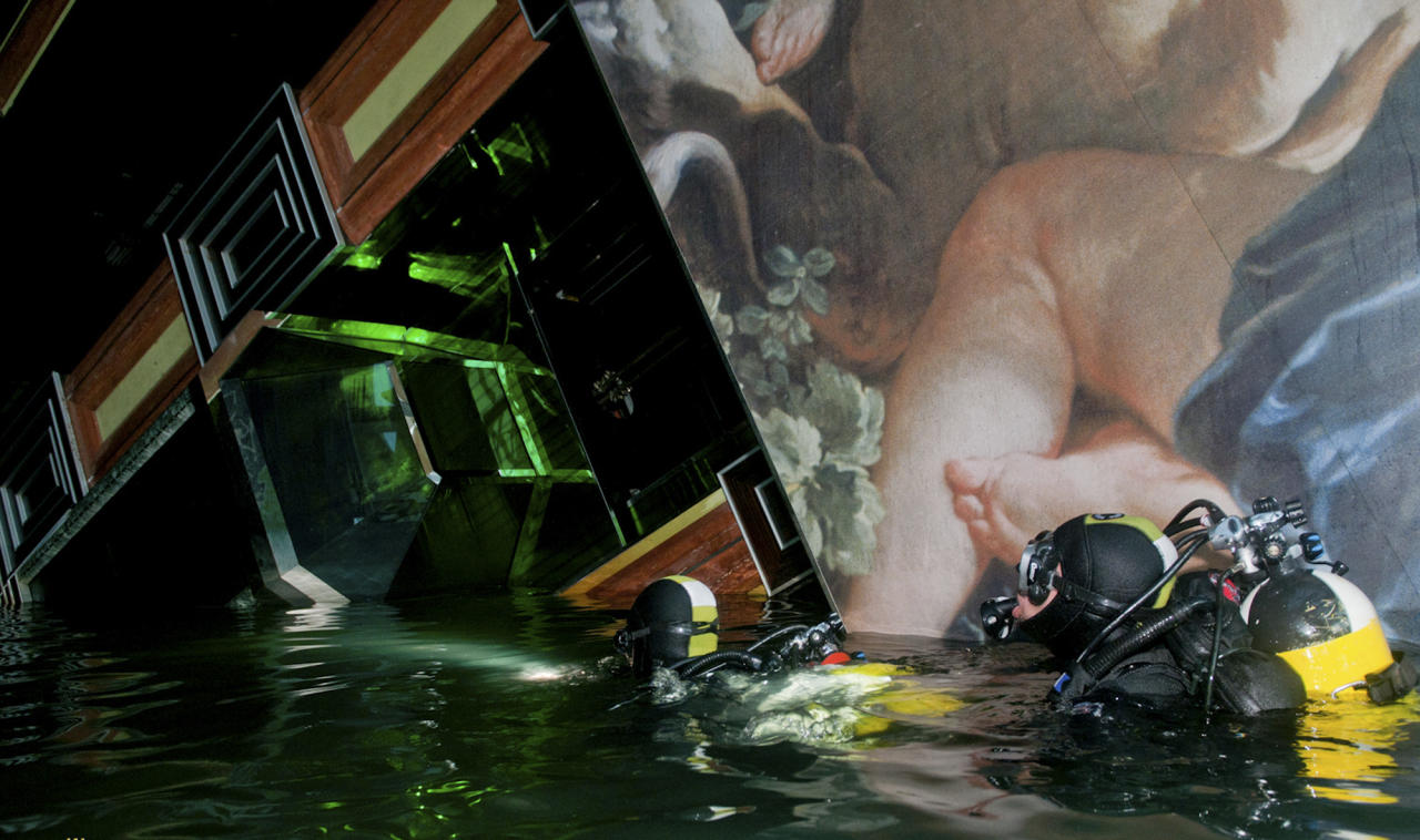 FILE In this undated photo released by the Italian Navy Tuesday, Jan. 24, 2012, scuba divers inspect the Costa Concordia cruise ship grounded off the Tuscan island of Giglio, Italy. A veritable treasure now lies beneath the pristine Italian waters where the massive cruise liner ran aground last month. In the chaotic evacuation of more than 4,200 people from the Costa Concordia, passengers and crew abandoned almost everything on board: jewels, cash, champagne, antiques, 19th century Bohemian crystal glassware, thousands of art objects and even 300-year-old woodcut prints by a Japanese master. (AP Photo/Italian Navy GOS handout)