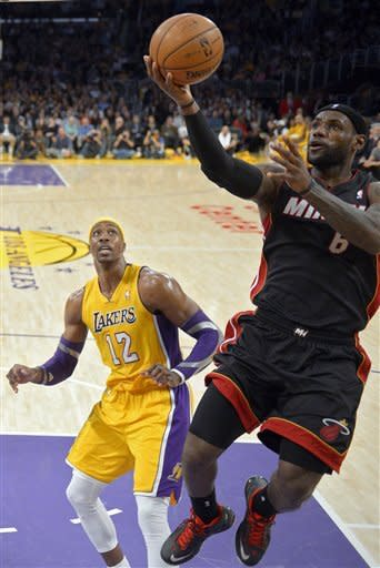 Miami Heat forward LeBron James, right, shoots as Los Angeles Lakers center Dwight Howard defends during the first half of their NBA basketball game on Thursday, Jan. 17, 2013, in Los Angeles. (AP Photo/Mark J. Terrill)