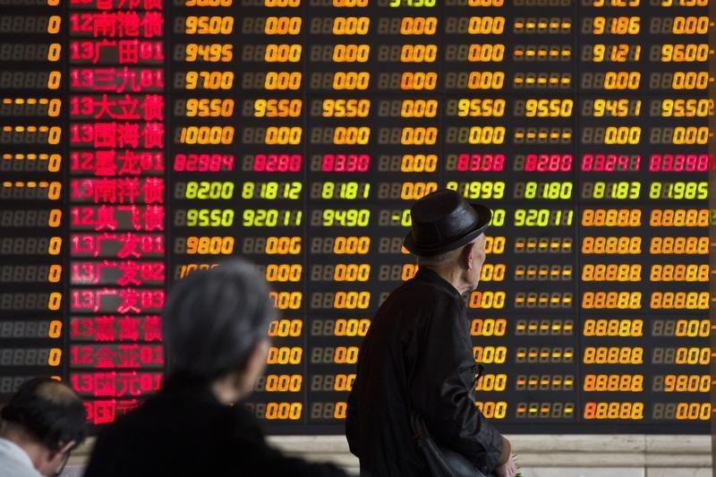 Investors look at information displayed on an electronic screen at a brokerage house in Shanghai
