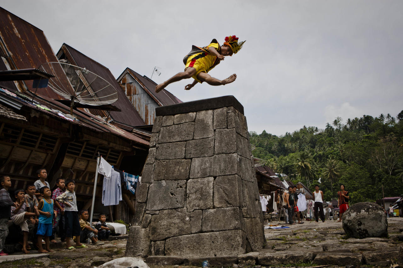 NIAS ISLAND, INDONESIA - FEBRUARY 24:  A villager wearing traditional costume jumps over a stone in front of their ancient houses in Orahili Fau village on February 24, 2013 in Nias Island, Indonesia. Stone Jumping is a traditional ritual, with locals leaping over large stone towers, which in the past resulted in serious injury and death. Stone jumping in Nias Island was originally a tradition born of the habit of inter tribal fighting on the island of Nias.  (Photo by Ulet Ifansasti/Getty Images)