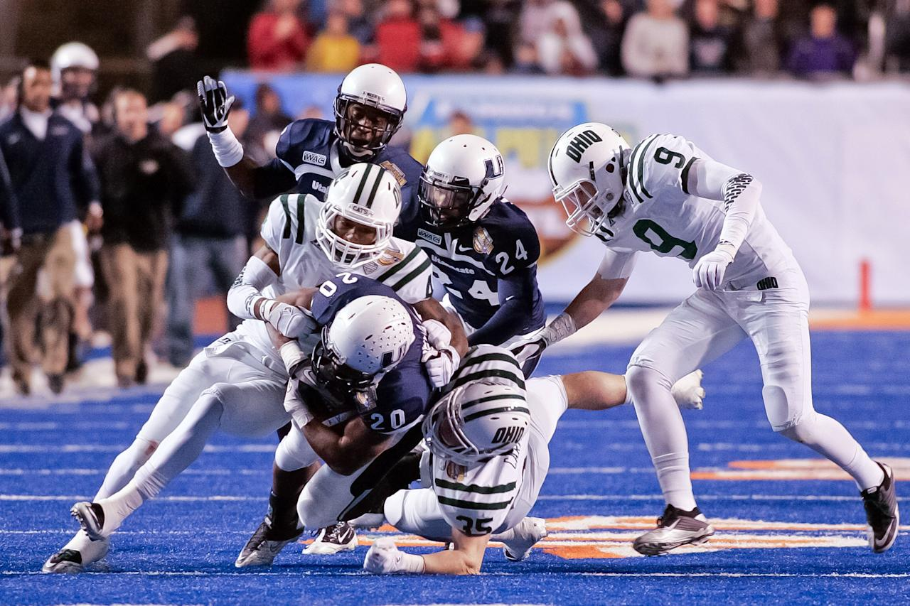 Michael Smith #20 of the Utah State Aggies is brought down by Omar Leftwich #4 and Nathan Carpenter #35 of the Ohio Bobcats at Bronco Stadium on December 17, 2011 in Boise, Idaho.  (Photo by Otto Kitsinger III/Getty Images)