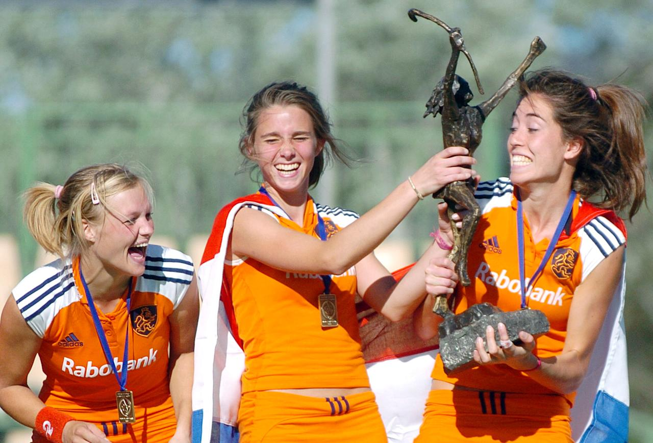 Sophie Polkamp, left, and Ellon Hoog, center, laugh as teammate Naomi Van As struggles to lift the trophy following their win over Australia in the final at the Champions Trophy women's field hockey tournament in Canberra, Australia, Sunday, Dec. 4, 2005. The Netherlands won in a penalty shoot-out after the score was locked at 0-0 at the end of the game. (AP Photo/Mark Graham)