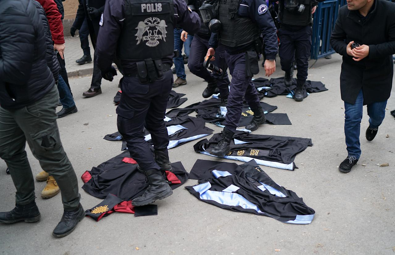 Riot policemen walk over gowns which were laid down by academics during a protest against the dismissal of academics from universities following a post-coup emergency decree, in the Cebeci campus of Ankara University in Ankara, Turkey, February 10, 2017. REUTERS/Umit Bektas