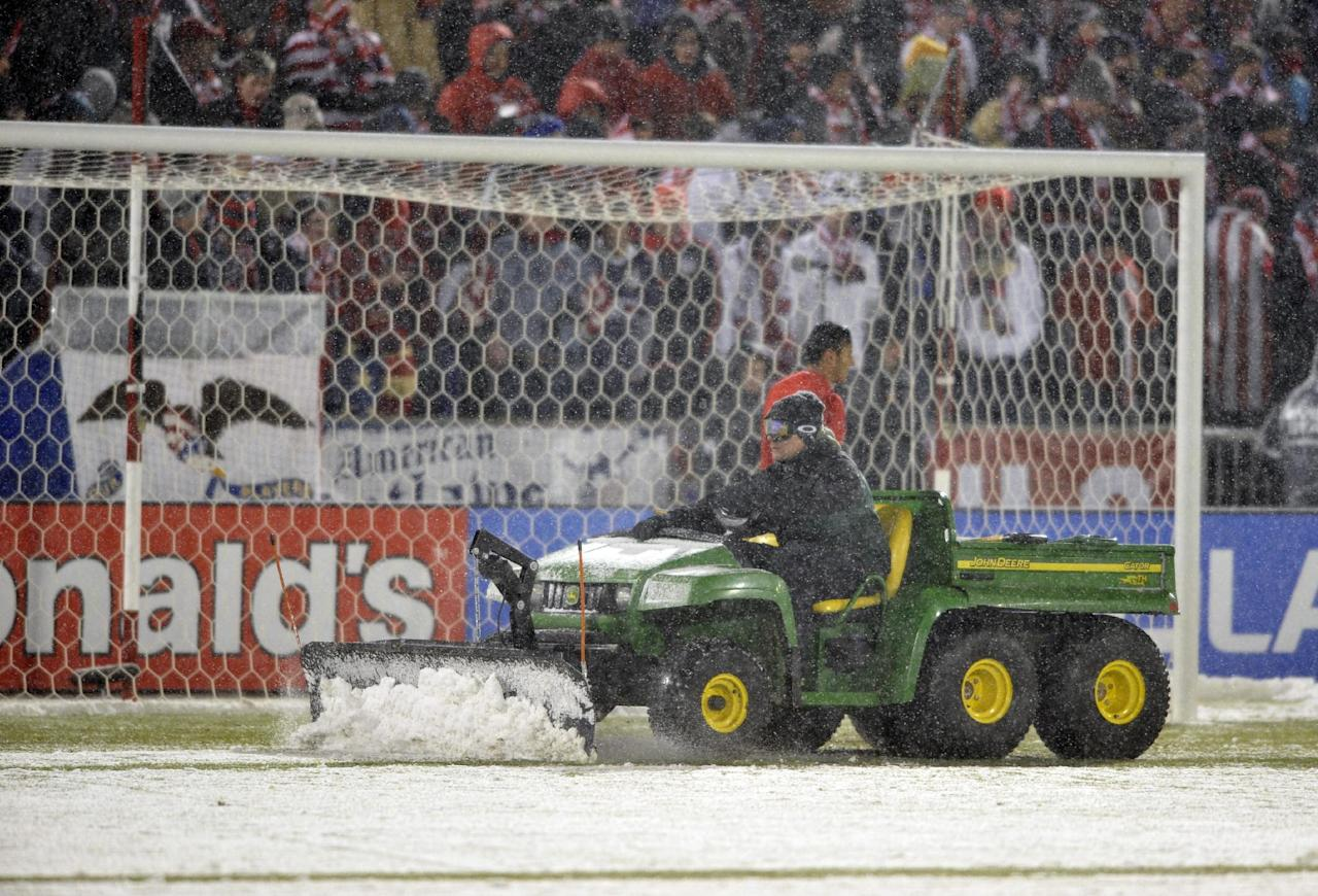 Maintenance crews plow snow from the field before the start of a World Cup qualifier soccer match between the United states and Costa Rica in Commerce City, Colo., Friday, March 22, 2013. (AP Photo/Jack Dempsey)