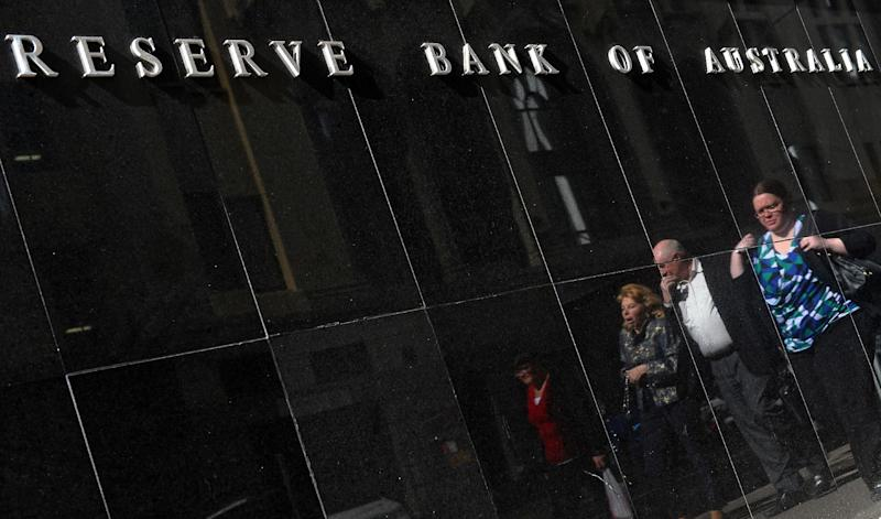 People walk past the Reserve Bank of Australia building in Sydney, on August 6, 2013