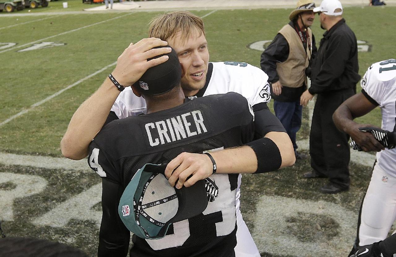 Philadelphia Eagles quarterback Nick Foles, rear, hugs Oakland Raiders wide receiver Juron Criner (84) after an NFL football game in Oakland, Calif., Sunday, Nov. 3, 2013. The Eagles won 49-20. (AP Photo/Marcio Jose Sanchez)