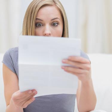 Shocked-woman-reading-letter-in-living-room_web