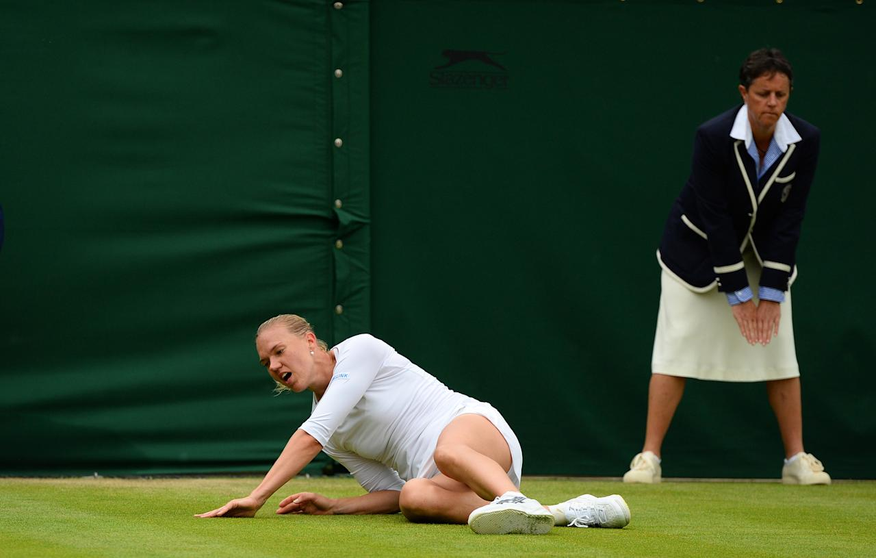 LONDON, ENGLAND - JUNE 28: Kaia Kanepi of Estonia slips whilst attempting to play a forehand during her Ladies' Singles second round match against Angelique Kerber of Germany on day five of the Wimbledon Lawn Tennis Championships at the All England Lawn Tennis and Croquet Club on June 28, 2013 in London, England. (Photo by Mike Hewitt/Getty Images)