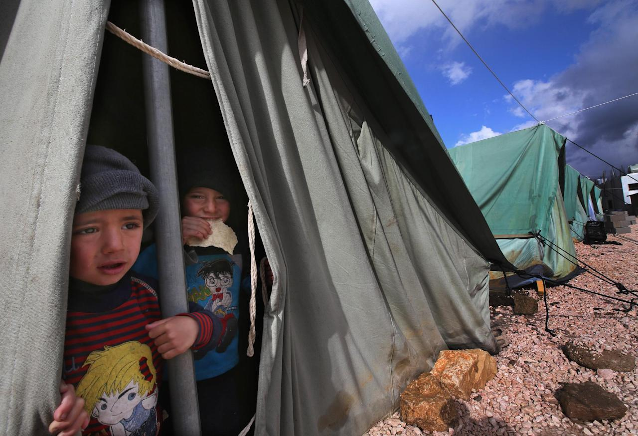 Syrian refugee boys look outside their tent, at a temporary refugee camp in the eastern Lebanese town of Marj near the border with Syria, Lebanon, Monday, Jan. 7, 2013. Syrian refugees worked on reinforcing their tents after they were flooded and some blown away by torrential rains and high winds. A heavy rainstorm coupled by snow on medium altitudes and high winds is hitting Lebanon causing material damage, flooding and trapping people in their cars. Particularly hard hit are thousands of Syrian refugees who fled to Lebanon, some of whom are staying in tents near the border with Syria. (AP Photo/Hussein Malla)