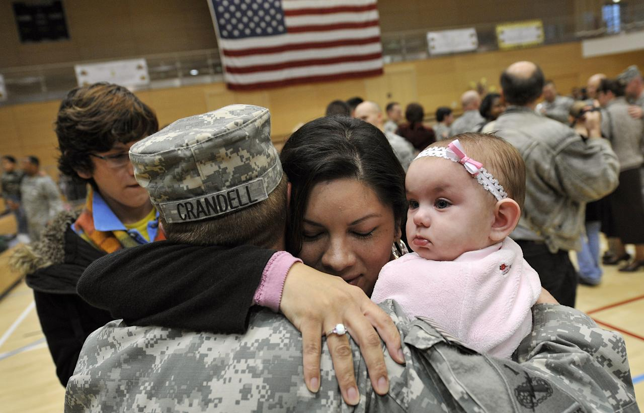 Sgt. Joseph Crandell of the U.S. 1st Armored Divison holds his seven month old daughter Lena for the first time as he hugs his wife Layla during a welcome home ceremony at the home base in Wiesbaden, Germany, November 25, 2008. The soldiers of the 1st AD returned on Tuesday from a 15month deployment to Iraq.  REUTERS/Kai Pfaffenbach (GERMANY)