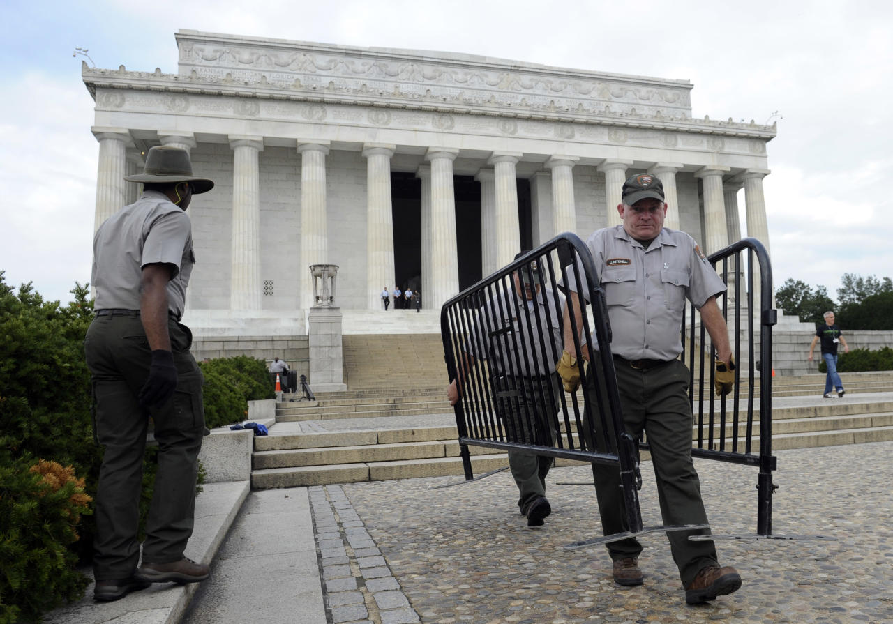 National Park Service employee James Mitchell, right, and others, remove barricades from the grounds of the Lincoln Memorial in Washington, Thursday, Oct. 17, 2013. Barriers went down at National Park Service sites and thousands of furloughed federal workers began returning to work throughout the country Thursday after 16 days off the job because of the partial government shutdown.(AP Photo/Susan Walsh)