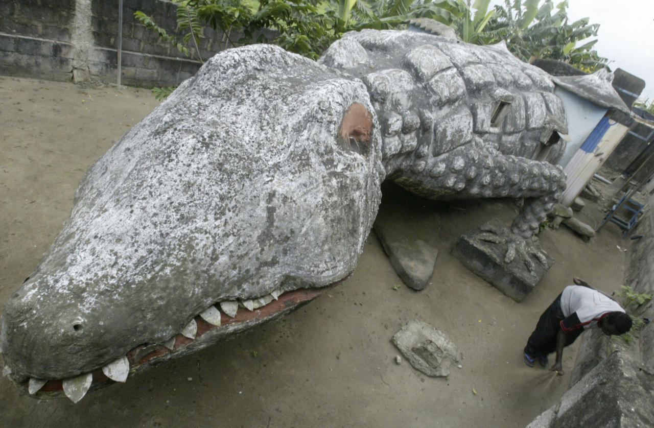 Thierry Atta sweeps the courtyard of his house built in the shape of a crocodile in Ivory Coast's capital Abidjan, September 11, 2008. Atta was an apprentice of the artist Moussa Kalo who designed and built the house but died two months ago.   REUTERS/Thierry Gouegnon (IVORY COAST) - RTX8O6X