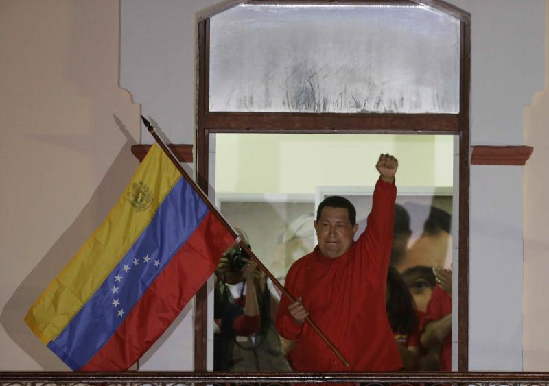 Venezuela's President Hugo Chavez waves a Venezuelan flag as he greets supporters at the Miraflores presidential palace balcony in Caracas, Venezuela, Sunday, Oct. 7, 2012.  Chavez won re-election and a new endorsement of his socialist project Sunday, surviving his closest race yet after a bitter campaign against opposition candidate Henrique Capriles.(AP Photo/Fernando Llano)