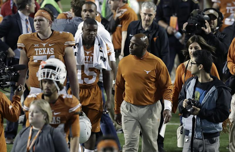 Texas coach Charlie Strong, center, looks to the stands as he walks off the field after the 31-9 loss to TCU. (AP Photo/Eric Gay)