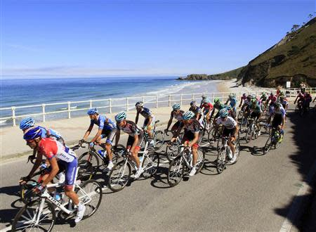 Cyclists ride near the sea during the 19th stage of the Vuelta, Tour of Spain cycling race from San Vicente de la Barquera to Alto del Naranco