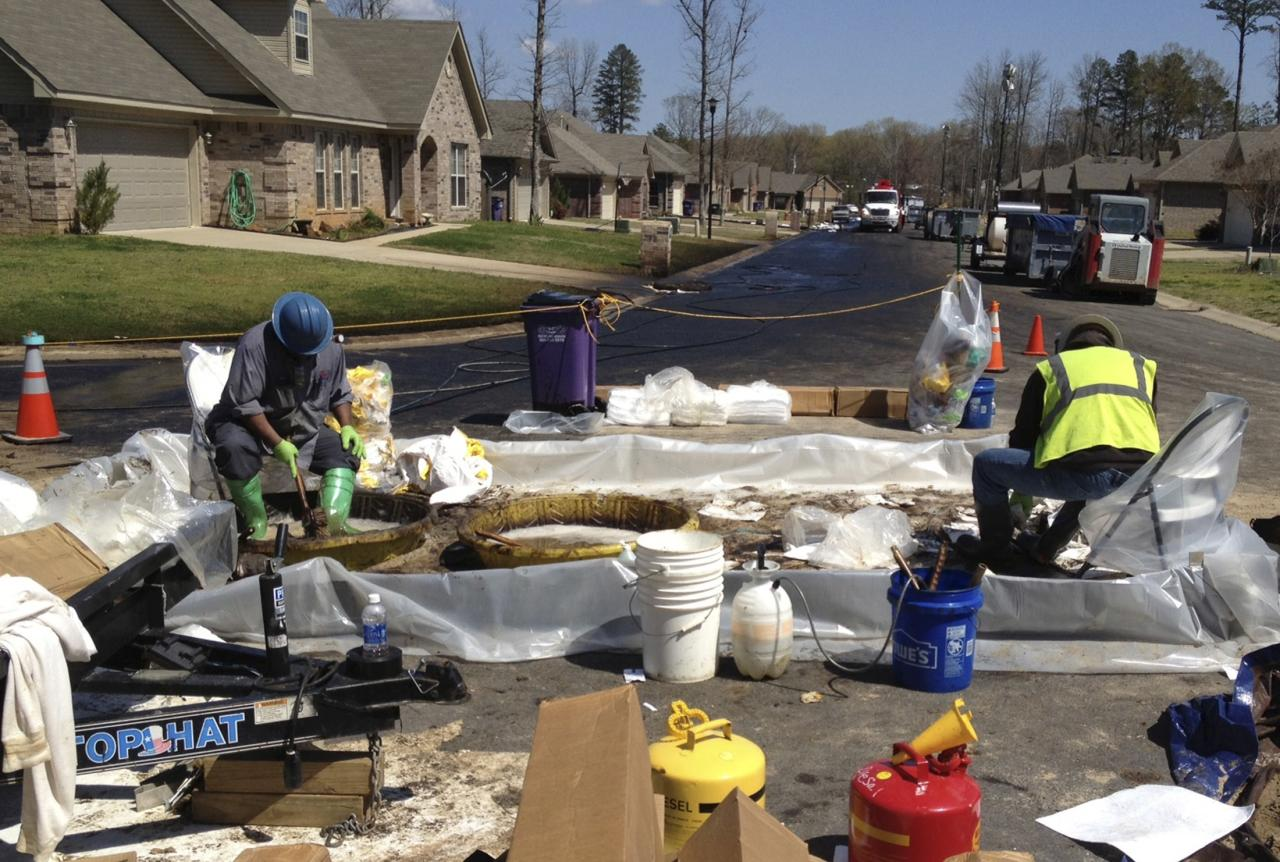 Workers scrub crude oil from their boots in the Northwoods subdivision where an ExxonMobil pipeline ruptured in Mayflower, Arkansas, in this April 1, 2013 file photo. Now, nearly two weeks after the 5,000-barrel spill occurred on Good Friday, a picture has emerged of a giant oil company thrust into a small blue-collar community, intricately managing not just the cleanup of a major spill, but also using its large check book to try to win over the townsfolk and seek to limit the fallout.  REUTERS/Suzi Parker/files  (UNITED STATES - Tags: DISASTER ENERGY ENVIRONMENT)