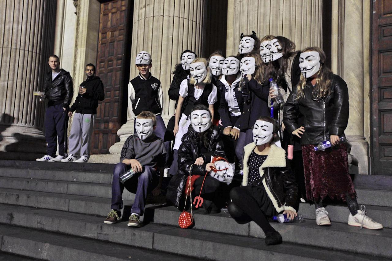 """A masked group of London school friends aged eleven and twelve pose for photographs for the media beside the Occupy London Stock Exchange protest camp outside St Paul's Cathedral in London, Thursday, Oct. 27, 2011. The children walked past the protest camp after going to a party together where they wanted to dress up as """"mini-anons"""". The plastic masks, which have been adopted by protesters in various countries around the world to keep their faces anonymous, represent Guy Fawkes, who attempted to blow up Britain's Houses of Parliament in the 1600s. (AP photo/Matt Dunham)"""