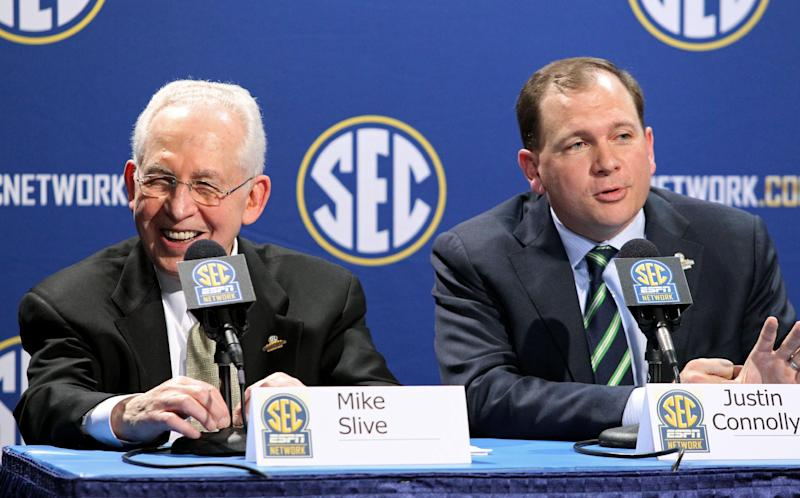 Southeastern Conference Commissioner Mike Slive, left, laughs as he listens to SEC Network President Justin Connolly, right, during a press conference the day before the SEC Football Championship game at the Georgia Dome, Friday, Dec. 6, 2013,  in Atlanta, Ga.,