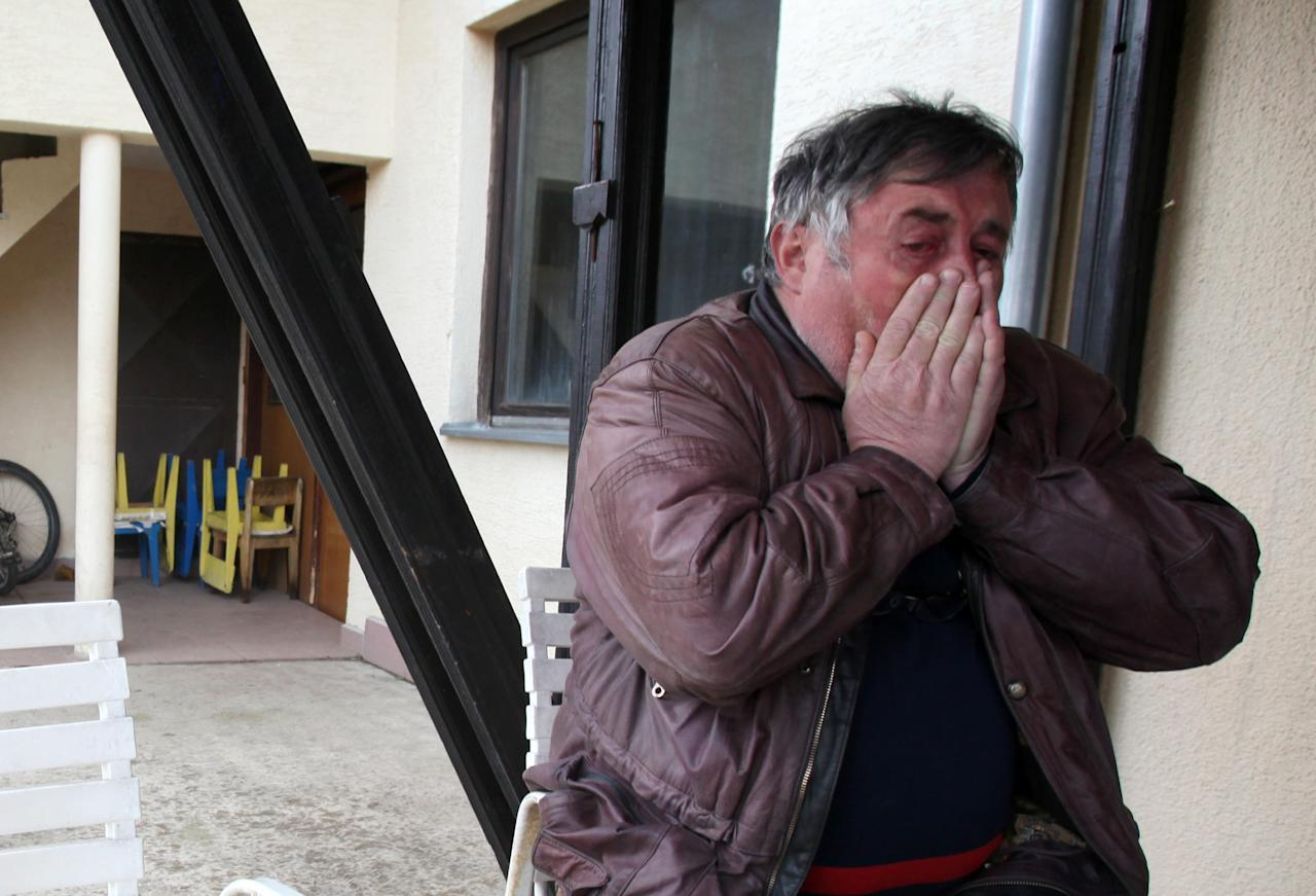 Radmilo Bogdanovic, brother of Ljubisa Bogdanovic cries in village of Velika Ivanca, Serbia, Tuesday, April 9, 2013. Ljubisa Bogdanovic a 60-year-old man gunned down 13 people, including a baby, in a house-to-house rampage in a quiet village on Tuesday before trying to kill himself and his wife, police and hospital officials said. Belgrade emergency hospital spokeswoman Nada Macura said the man, identified as Ljubisa Bogdanovic, used a handgun in the shooting spree at five houses. The dead included six women. (AP Photo/Darko Vojinovic)