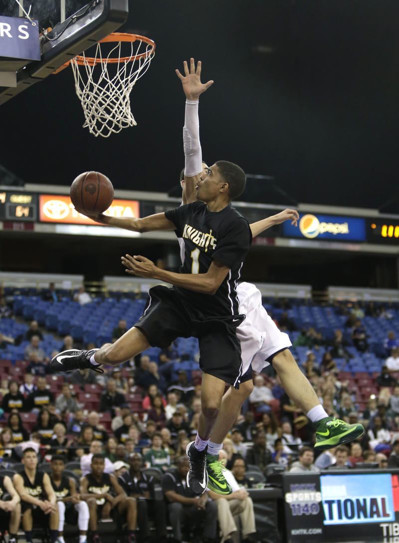 Bishop Montgomery guard Stephen Thompson, left, drives to the basket against Moreau Catholic guard Brandon Lawrence during the fourth quarter of the boys' Division 4 CIF basketball championship game Saturday, March 29, 2014, in Sacramento, Calif. Bishop Montgomery won 85-44