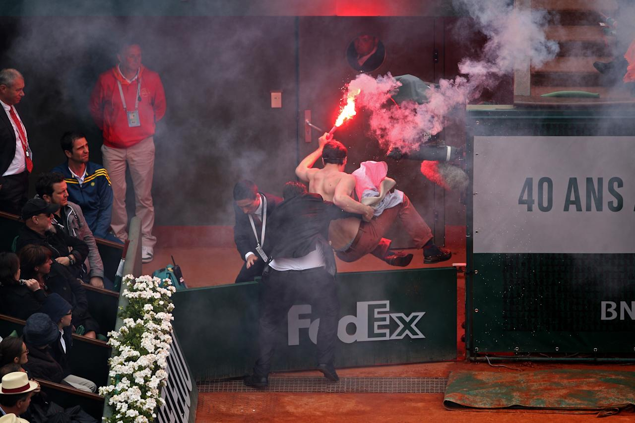 PARIS, FRANCE - JUNE 09: A protester is thrown over one of the court gates after he lit a flare and ran on court before the start of a game in the Men's Singles final match between Rafael Nadal of Spain and David Ferrer of Spain during day fifteen of the French Open at Roland Garros on June 9, 2013 in Paris, France. (Photo by Clive Brunskill/Getty Images)