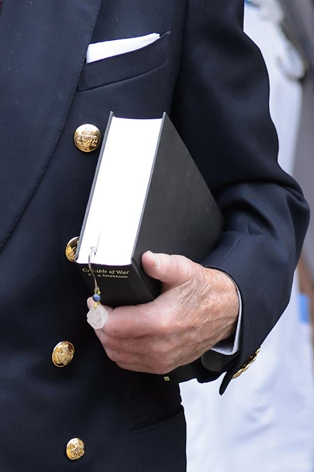 """The Duke of Edinburgh carries a book entitled """"Crucible of War"""" by Fred Anderson as he leaves the London Clinic in central London, 11 days after he was admitted for exploratory abdominal surgery."""