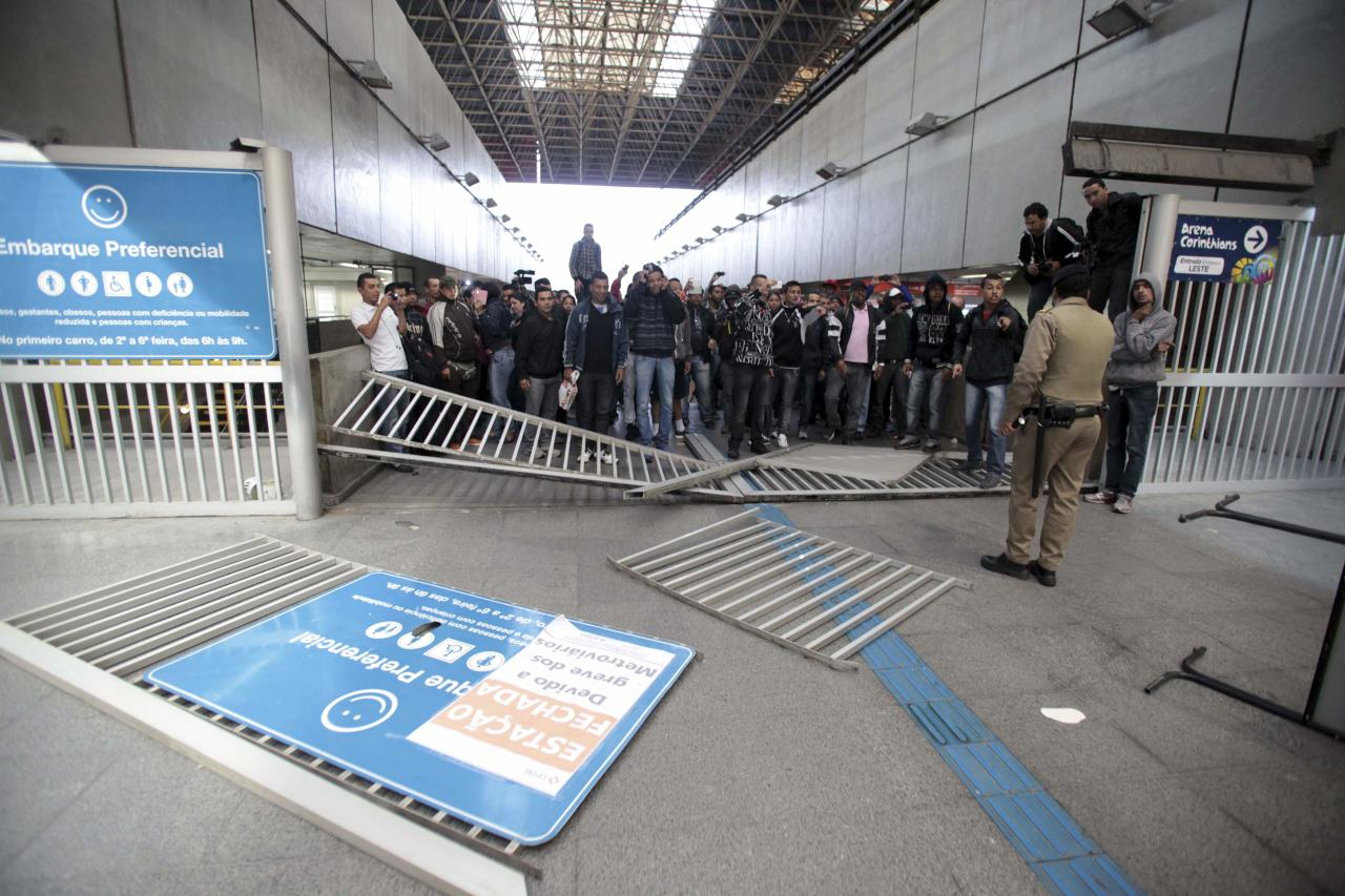A police officer looks at commuters behind an entrance gate broken by the commuters at Itaquera subway station in Sao Paulo June 5, 2014. Union workers of Sao Paulo's Metro subway system are on strike since midnight, with just a week to go before the 2014 World Cup opens in Brazil, local media reported. The commuters broke the gate, which was closed due to the strike, to get access to the train to go to work. REUTERS/Chico Ferreira (BRAZIL - Tags: TPX IMAGES OF THE DAY SPORT SOCCER WORLD CUP CIVIL UNREST POLITICS TRANSPORT)