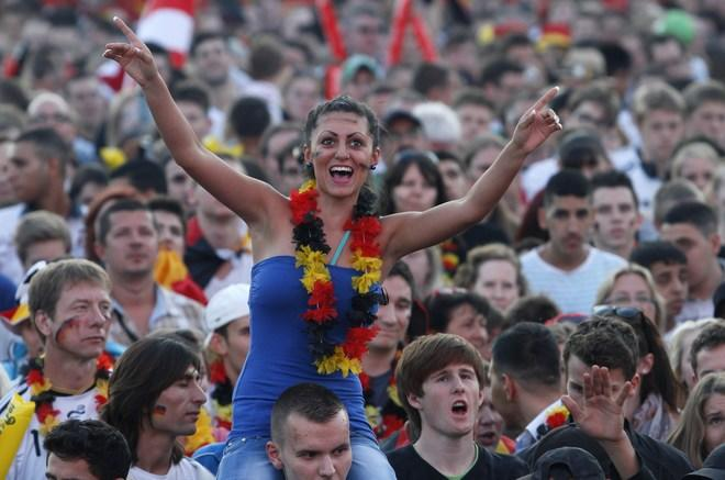 """Supporters of the German national football team cheer up their team during the public screening of Germany's opening match against Portugal in the Euro 2012 football championships at the """"Fanmeile"""" (Fan Mile) in Berlin on June 9, 2012. AFP PHOTO / MICHELE TANTUSSIMICHELE TANTUSSI/AFP/GettyImages"""