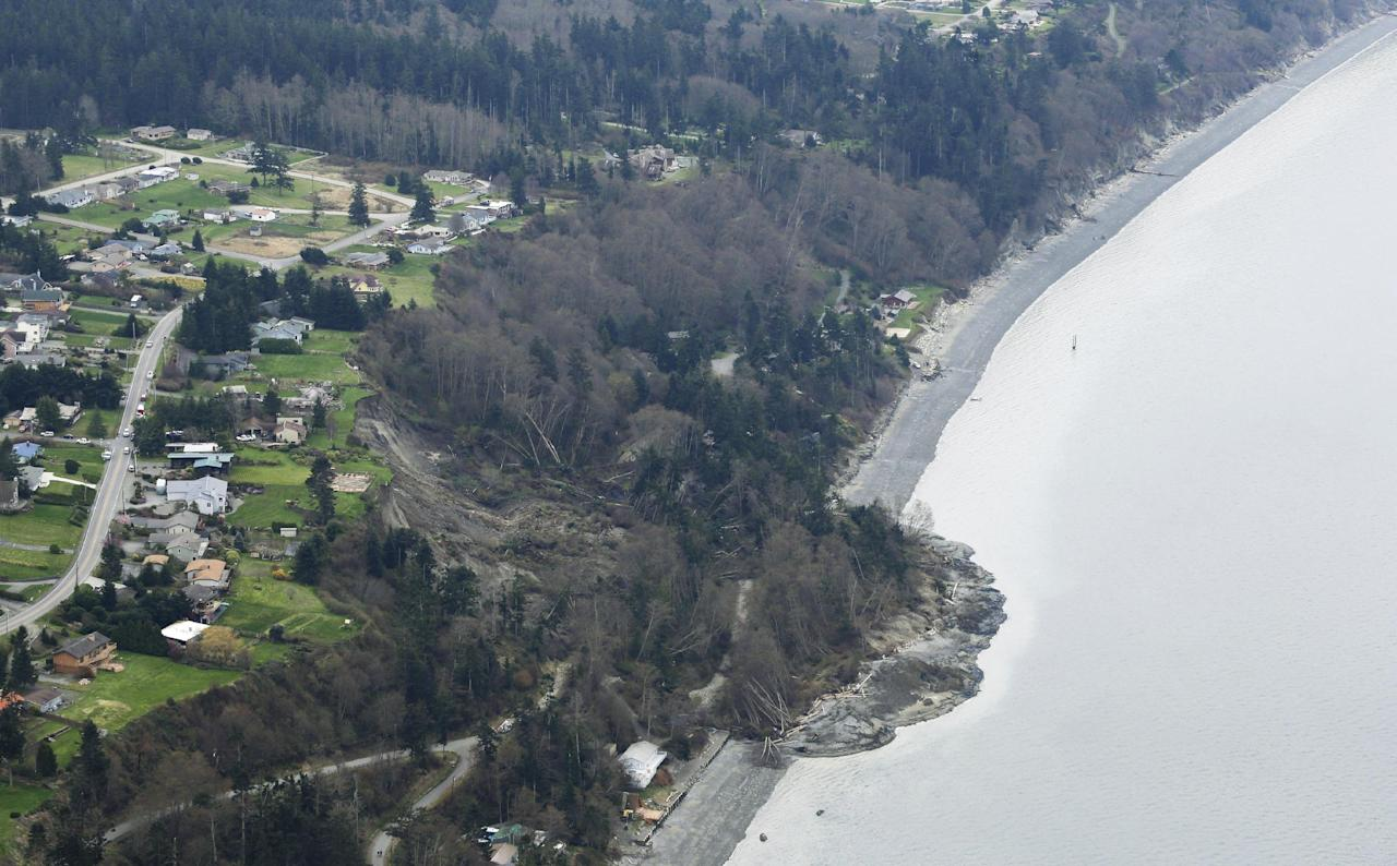 An aerial photo shows a landslide near Coupeville, Wash. on Whidbey Island, Wednesday, March 27, 2013. The slide severely damaged one home and isolated or threatened more than 30 on the island, about 50 miles north of Seattle in Puget Sound. No one was reported injured in the slide, which happened at about 4 a.m. Wednesday. (AP Photo/Ted S. Warren)