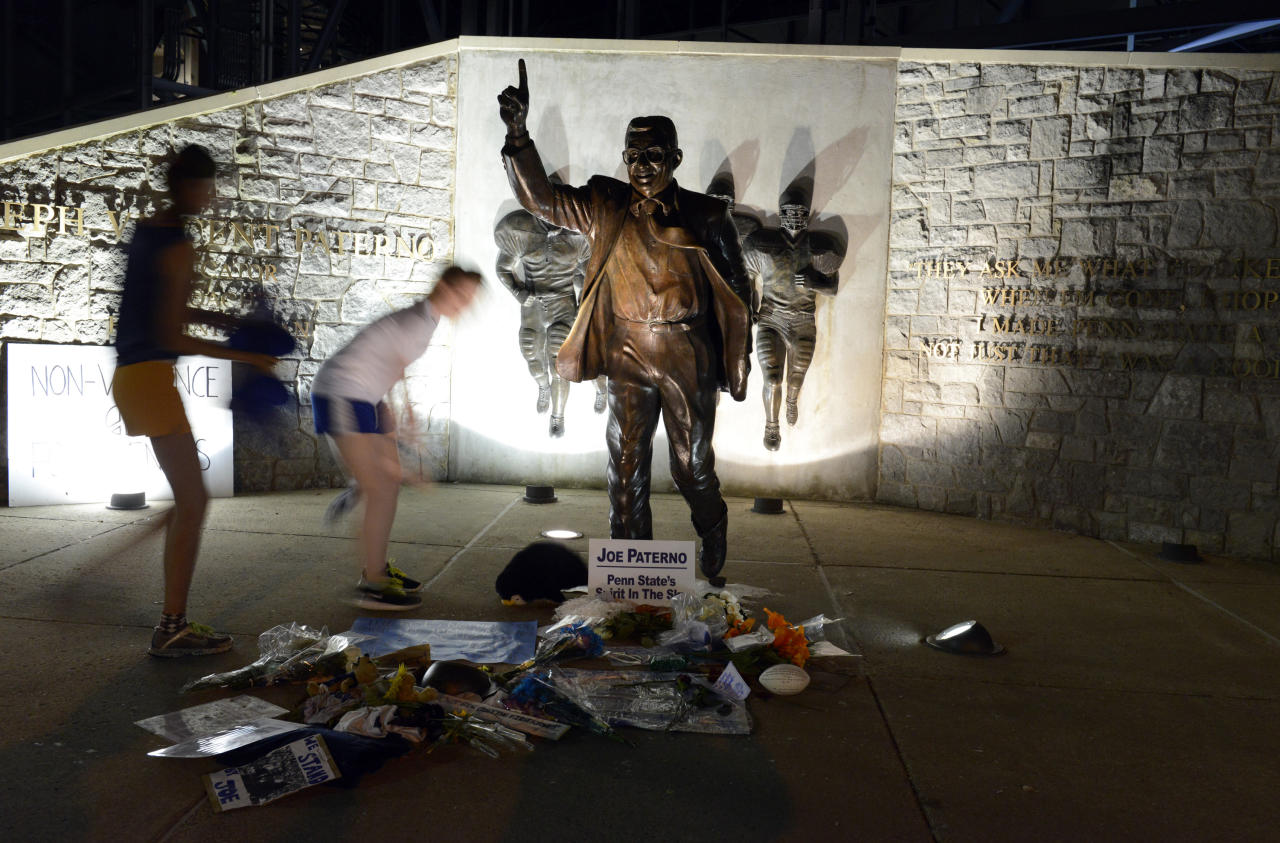 People visit the Joe Paterno statue early Sunday July 22, 2012. in State College, Pa. The famed statue of Paterno was taken down from outside the Penn State football stadium Sunday morning, eliminating a key piece of the iconography surrounding the once-sainted football coach accused of burying child sex abuse allegations against a retired assistant. (AP Photo/John Beale)