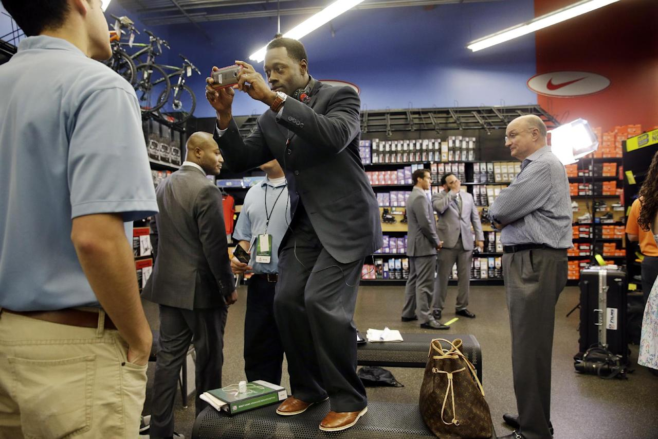 In this photo taken on Wednesday, June 18, 2014, former NFL football player, safety Nick Ferguson, stands on a bench to take photos as former first-round draft pick, quarterback Brady Quinn, center left, and fellow NFL football player, defensive tackle Antonio Garay, center right, work on an interview at a sporting goods store during the NFL's Broadcast Boot Camp in Mount Laurel, N.J. Twenty-five current and former players participating in the NFL's Broadcast Boot Camp this week, are vying for broadcasting gigs. (AP Photo/Mel Evans)