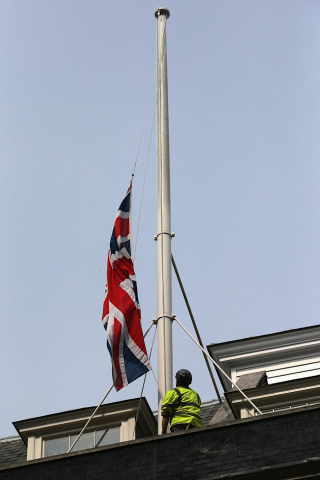LONDON, ENGLAND - APRIL 08:  A workman lowers the Union Flag flying above Downing Street to half-mast at the news of the death of former British prime Minster Baroness Thatcher on April 8, 2013 in London, England. It has been confirmed that Lady Thatcher has died this morning following a stroke aged 87. Margaret Thatcher was the first female British Prime Minster and governed the UK from 1979  to 1990. She led the UK through some turbulent years and contentious issues including the Falklands War, the miner's strike and the Poll Tax riots.  (Photo by Oli Scarff/Getty Images)
